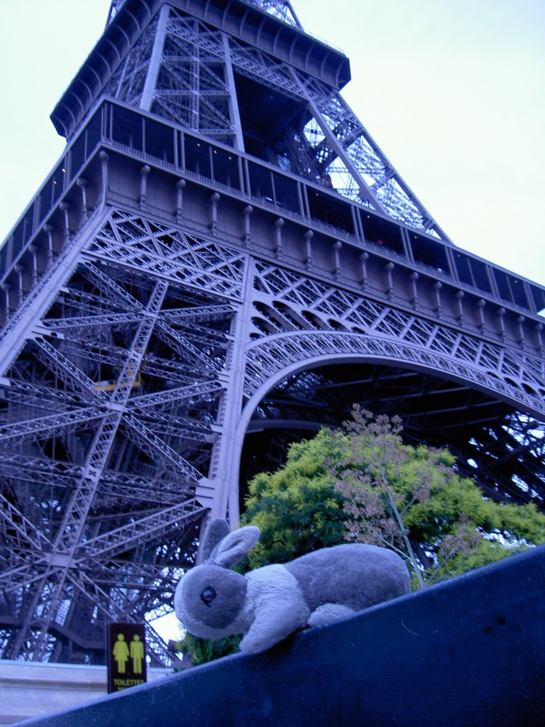 A photo of a stuffed rabbit standing next-to/under the Eiffel Tower